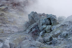White toxic steam raising behind big colored rock in Iceland Royalty Free Stock Photos