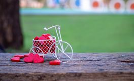 White toy bike carrying red wood hearts. Red wood hearts fall on the wooden floor, green background of grass. Heart-shaped toys. Convey to Valentine`s Day royalty free stock image