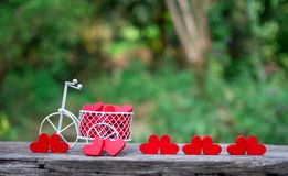 White toy bike carrying red wooden hearts. Red wood hearts fall on the wooden floor. Heart-shaped toys convey to Valentine`s Day. White toy bike carrying red royalty free stock photos