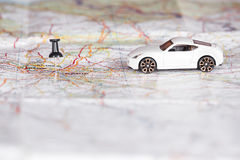 White toy car with a black pin on a map. Shallow depth of field. Royalty Free Stock Photo