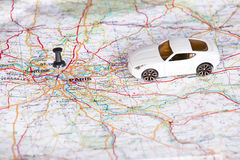 White toy car and a black pin on a map. Shallow depth of field. Stock Photos