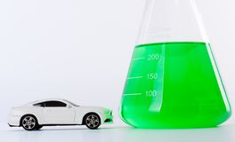 Transportation & Fuel. Closeup view showing a white toy car parked in front of a glass Erlenmeyer flask filled with green liquid. BIO fuel, flex fuel concept royalty free stock photo