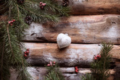 White toy-heart on wooden planks with spruce branches and red berries all around. Royalty Free Stock Photos