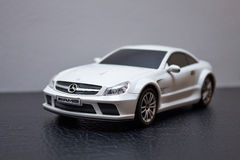 White toy Mercedes-Benz AMG SL 65. Collectible white toy Mercedes-Benz AMG SL 65 isolated on grey and black background Royalty Free Stock Photography