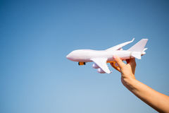 White toy plane in female hand on sunny blue sky Stock Photos