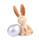 White toy rabbit with silver egg. Royalty Free Stock Photos