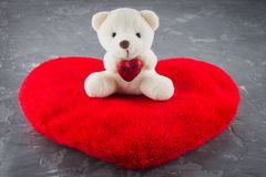 White toy teddy bear with heart on a gray background. The symbol of the day of lovers. Valentine's Day. Concept February 14. royalty free stock images