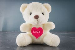 White toy teddy bear with heart on a gray background. The symbol stock photography