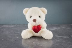 White toy teddy bear with heart on a gray background. The symbol of the day of lovers. Valentine's Day. Concept February 14. stock photos