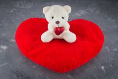 White toy teddy bear with heart on a gray background. The symbol royalty free stock photos