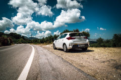 White Toyota Auris stays parked among clouds on road of Crete island. Stock Photos