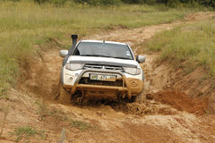 White Toyota Triton DHD crossing mud obstacle Stock Photo