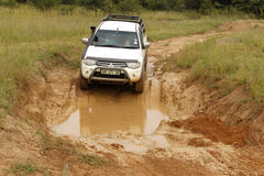 White Toyota Triton DHD crossing mud obstacle Royalty Free Stock Photography