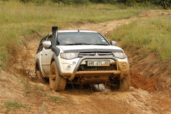 White Toyota Triton DHD crossing mud obstacle Stock Image