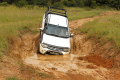 White Toyota Triton DHD crossing mud obstacle Royalty Free Stock Image