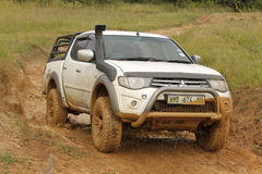 White Toyota Triton DHD crossing mud obstacle Royalty Free Stock Photo