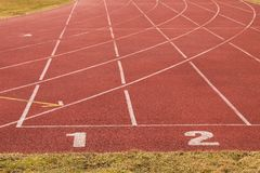 White track number on red rubber racetrack, texture of running racetracks in small outdoor stadium Stock Images
