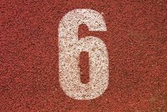 White track number on red rubber racetrack, texture of running racetracks in small outdoor stadium Royalty Free Stock Image