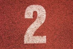 White track number on red rubber racetrack, texture of running racetracks in small outdoor stadium Stock Photos