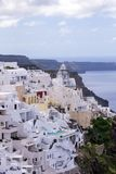 White traditional Greek houses on a hillside on the island of Santorini. Beautiful view of the sea, the ship, the volcano and buil royalty free stock photos