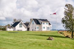 White traditional Norwegian house, the flag on the mast Stock Images