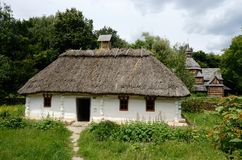 White traditional Ukrainian rural wooden house with hay roof Stock Images