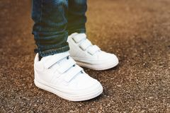 White trainers on child`s feet. Close up of white trainers on child`s feet Royalty Free Stock Images