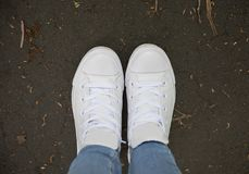 White trainers on a foot path. Outdoors Stock Photo