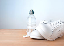 White trainers water bottle on wooden plank. White sport trainers shoes water bottle earphones on wooden plank Royalty Free Stock Image