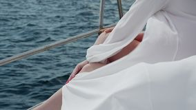 White transparent tunic fluttering in the wind. lightweight sun robe on the shoulders of a young woman Light sea breeze