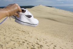 White traveler& x27;s sneakers on the background of Pilat dune, the largest sand dune in Europe. White traveler& x27;s sneakers on the background of Pilat Royalty Free Stock Photos