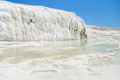 White travertine terrace and waterfall against blue sky Stock Photos