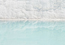 White travertine wall reflecting in turquoise pool Royalty Free Stock Image