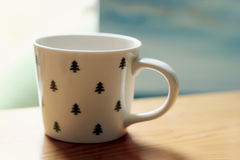 White tree patterned cup on table Stock Images