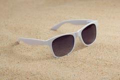 White trendy sunglasses on beach sand Royalty Free Stock Photo