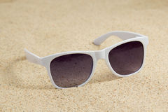 White trendy sunglasses on sandy beach Royalty Free Stock Photos