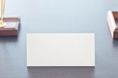 White triangular sign for the label standing on a black table. Stock Image