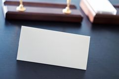 White triangular sign for the label standing on a black table. Royalty Free Stock Photography