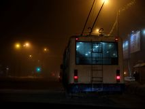 White trolleybus driving dangerously in the fog at night stock photo