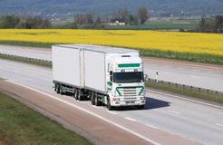 White truck. White truck on the highway. Yellow fields in the background Stock Photos