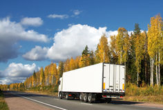 White truck on autumn highway. Scandinavia, landscape stock photos