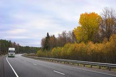 White truck on autumn highway Stock Image