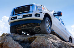 White truck on cliff edge showing undercarriage Royalty Free Stock Images