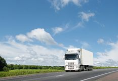 White truck on  country highway under blue sky. White truck on  summer country highway under blue sky, landscape Royalty Free Stock Photos