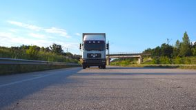 White truck driving on a highway. Lorry rides through the countryside with beautiful landscape at background. Slow