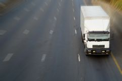 White truck on highway. White big delivery or logistics truck on highway road with motion blur showing speed Stock Photo