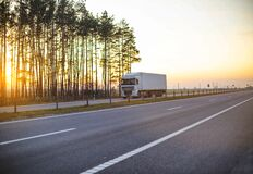 White truck with isotherm semitrailer transports frozen fruits and vegetables on the highway against the backdrop of a sunny