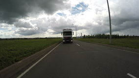White truck moves along asphalt road among landscape stock video