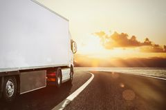 White truck moving on the road in a natural landscape at sunset. Moving truck in a natural landscape background stock images