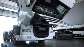 White Truck with open hood at the service station during the annual maintenance